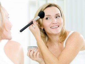 woman applying makeup powder