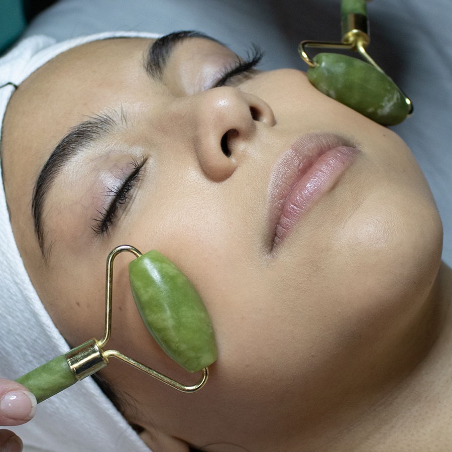 Student receiving facial treatment with jade rollers in student clinic.
